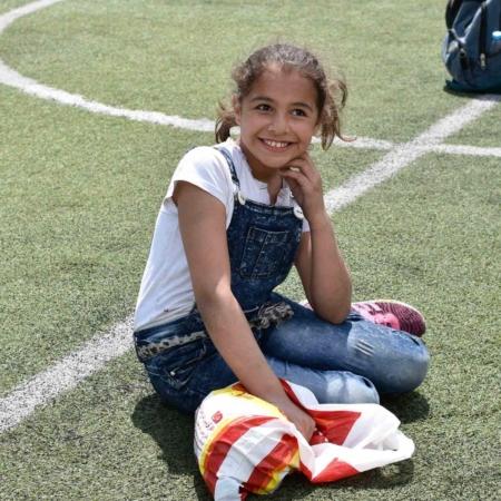 Ein geflüchtetes Mädchen aus Jordanien freut sich über das Sportangebot