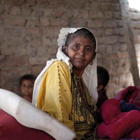 Familie in Pakistan, Frau, zwei Kinder im Hintergrund, in einem Haus