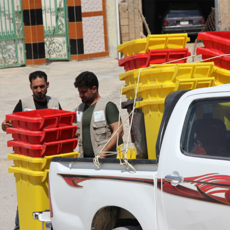 Ankunft von neuen Mülltonnen im irakischen Bezirk