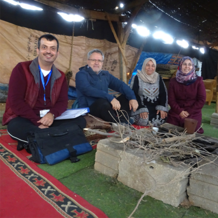 Mitarbeiter in dem Zelt, sitzend mit Einheimischen
